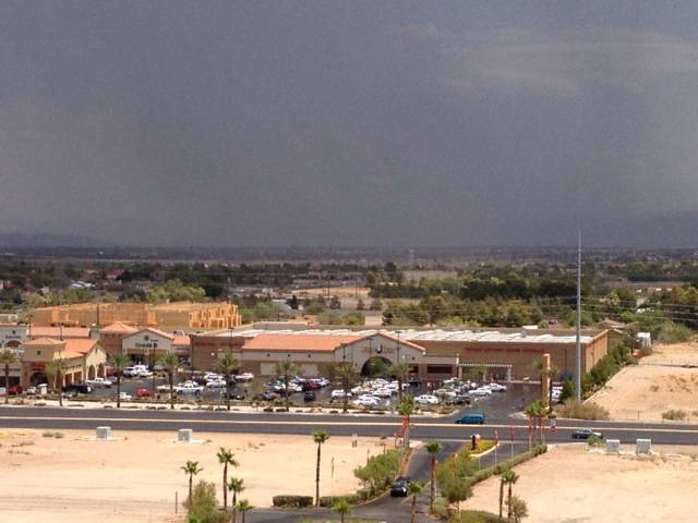 As the western Las Vegas Valley experienced sunshine early Sunday afternoon, thunderstorms rolled through Henderson and eastern Las Vegas. This image, facing northeast, shows a strip mall at Las Vegas Boulevard and Windmill Lane in the foreground.