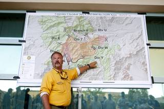 Rod Collins, an operation section chief for the National Incident Management Team briefs the night shift firefighters before they head out to the Carpenter 1 wildfire from Centennial High School on Monday, July 8, 2013.