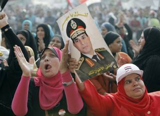 Egyptians chant slogans as they hold a poster of Egyptian Army Chief Lt. Gen. Abdel-Fattah el-Sissi during a protest in Tahrir Square in Cairo, Egypt, Monday, July 8, 2013. Egyptian soldiers and police opened fire on supporters of the ousted president early Monday in violence that left dozens of people killed, including one officer, outside a military building in Cairo where demonstrators had been holding a sit-in, government officials and witnesses said. Arabic reads: