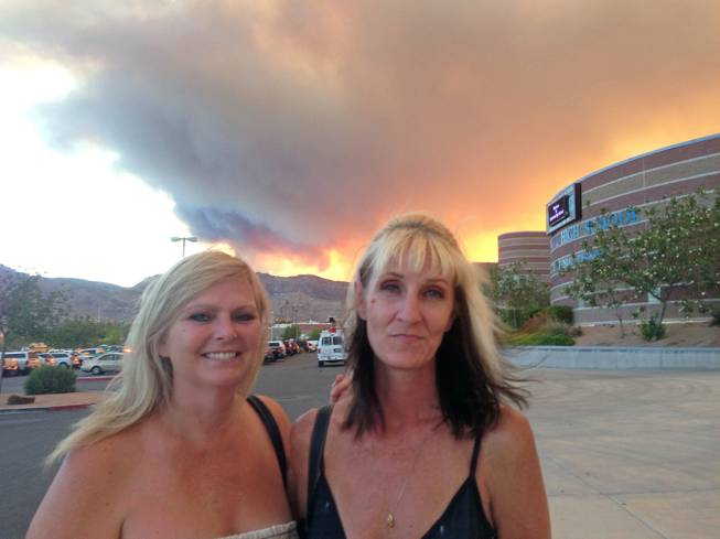 Kim Coster, right, and Kerri Paniagua were among the Mount Charleston evacuees who attended an informational meeting at Centennial High School on Monday night, July 8, 2013. Smoke from the vast wildfire turned a bright, fiery orange as the sun began to set behind the Spring Mountains.