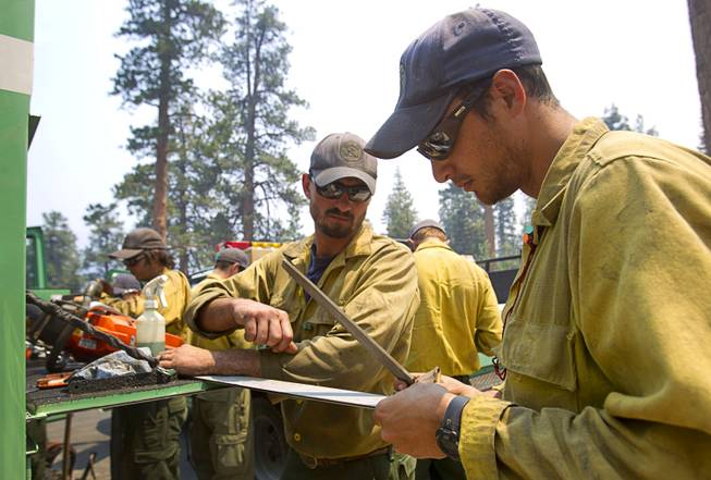Evan, O'Shea, center, and Sean Alvarez, right, members of the Stanislaus Hot Shots based in Sonora, Calif., work on a chainsaw on Mount Charleston Tuesday, July 9, 2013.