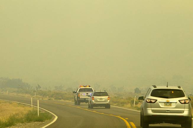 A Metro Police pickup truck leads a media convey through wildfire smoke on Kyle Canyon Road after a tour of fire activities on Mount Charleston Tuesday, July 9, 2013.