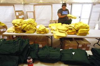Holly Thomas looks for a particular size of firefighting clothing at a clothing exchange for firefighters working the Mt. Charleston fire Wednesday, July 10, 2013 at Centennial High School.