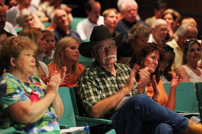 "Royce ""Woody"" Wood and other evacuated residents applaud while being briefed on the progress of fighting the Mt. Charleston fire Wednesday, July 10, 2013 at Centennial High School."