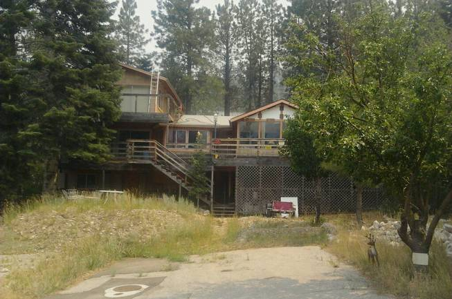 A view of the Mount Charleston home of Rodney Giles, who chose not to evacuate his residence despite a nearby wildfire, Tuesday, July 9, 2013.