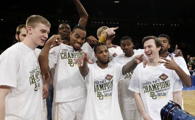 Baylor's Pierre Jackson, center, poses for photographs with teammates after the NIT championship basketball game against Iowa on Thursday, April 4, 2013, in New York. Baylor won 74-54.