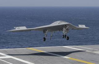 A X47-B Navy drone approaches the deck as it lands aboard the nuclear aircraft carrier USS George H. W. Bush off the Coast of Virginia Wednesday, July 10, 2013.