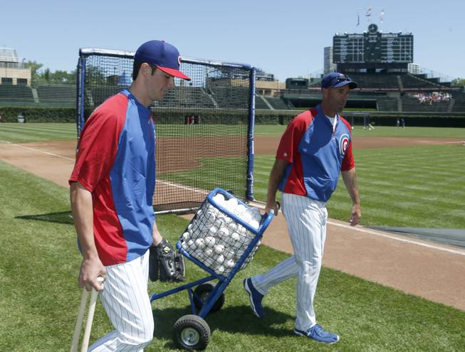 Chicago Cubs' first-round draft pick Kris Bryant, left, walks out to the field as he takes batting practice with manager Dale Sveum before a baseball game against the St. Louis Cardinals Friday, July 12 2013, in Chicago.
