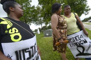 Lashauna Banks, left, of Gainesville, Fla., watches as her mother, Tara Banks, right, is consoled by Julie Yvette May, of Gordon, Ga. during a rally for Trayvon Martin outside the grounds of the Seminole County Courthouse in Sanford, Fla., Sunday, July 14, 2013. George Zimmerman was found not guilty in the 2012 shooting death of Martin.