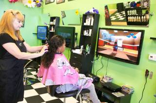 Hair stylist Cassie Briggs performs a cut and style while her client plays on a Playstation 3 at Sharkey's Cuts for Kids, a Henderson based hair salon for childen, Monday July 15, 2013.