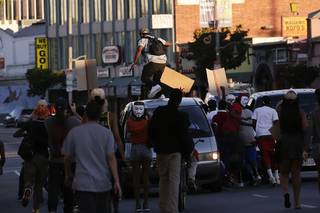 A protester stomps on a van during a demonstration in reaction to the acquittal of neighborhood watch volunteer George Zimmerman on Monday, July 15, 2013, in Los Angeles. Anger over the acquittal of a U.S. neighborhood watch volunteer who shot dead an unarmed black teenager continued Monday, with civil rights leaders saying mostly peaceful protests will continue this weekend with vigils in dozens of cities.