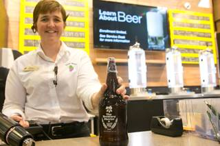 Melissa Long-Higgs, store manager for Total Wine & More on North Stephanie St., fills up a beer growler at their Brewery District inside their store, Wednesday July 17, 2013.