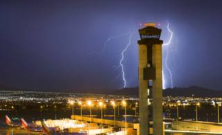 Lightning strikes south of McCarran International Airport as a storm makes its way across the Las Vegas Valley Friday, July 19, 2013.