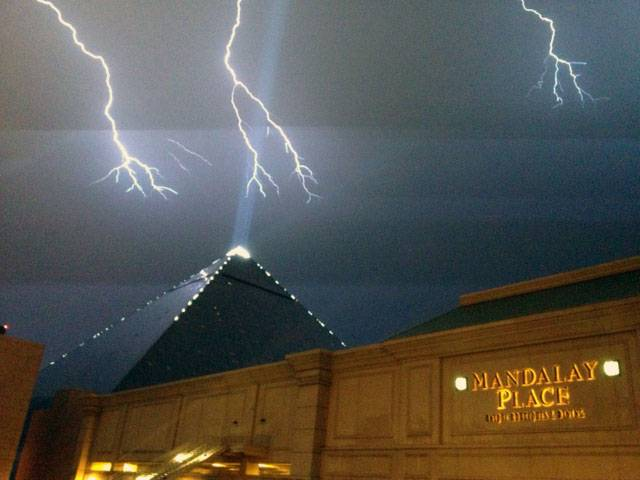 Lightning strikes over Mandalay Bay and the Luxor, Friday, July 19, 2013.