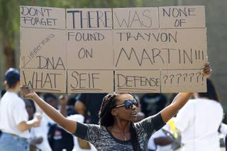 Vena Davis holds a sign during a rally on the one week anniversary of George Zimmerman's acquittal in the killing of Trayvon Martin Saturday, July 20, 2013.