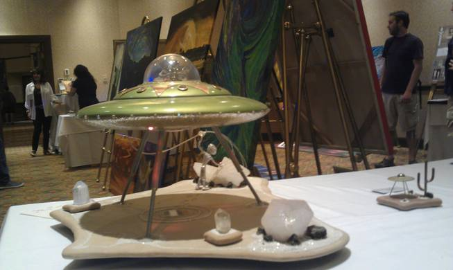 "UFO art on display at the annual Mutual UFO Network Symposium at the JW Marriott Las Vegas Resort on Sunday morning. The green sculpture in the foreground, entitled ""Power"", was created by amauter artist Michael Harley, who said the work took several months to complete. Harley said the piece, which was priced at $600, came from his imagination and was created out of porcelain plates and LED lighting. The conference featured art from 10 different artists, each with a unique spin on alien-inspired artwork."