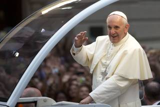 Pope Francis waves from his popemobile as he makes his way into central Rio de Janeiro, Brazil, Monday, July 22, 2013. The pontiff arrived for a seven-day visit in Brazil, the world's most populous Roman Catholic nation. During his visit, Francis will meet with legions of young Roman Catholics converging on Rio for the church's World Youth Day festival.