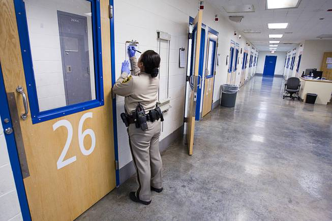 A corrections officer fills out out a log after visually checking on an inmate in a special housing area during a tour of the Clark County Detention Center Tuesday, July 23, 2013.