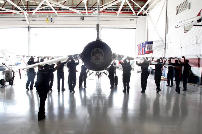 Crew members move an F-16 in the Thunderbird hangar as the Thunderbirds resume limited flight operations at Nellis Air Force Base Tuesday, July 22, 2013 after having to stand down since April because of sequestration.