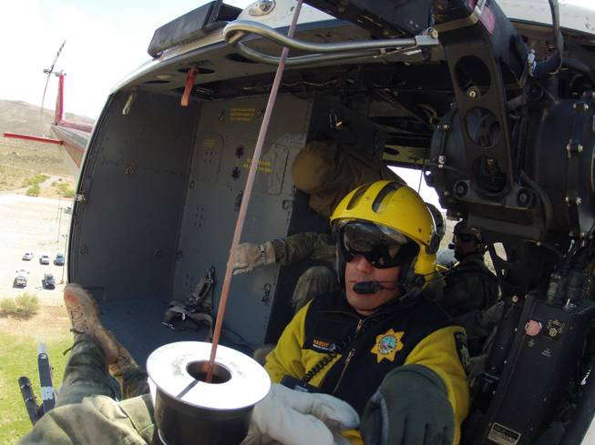 Metro Police Officer David Vanbuskirk, who died Monday while rescuing a stranded hiker, is shown riding in a helicopter near Bonnie Springs in May 2013 while helping train Drug Enforcement Administration agents.