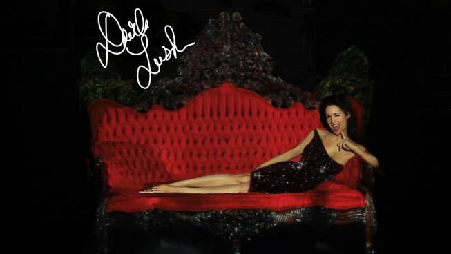Although completely nude, burlesque performer Darla Lush appears to be clothed using projection mapping technology at the El Cortez on Tuesday, July 23, 2013.  She plans to incorporate the technology into her striptease act. The couch she is sitting on is also projection mapped -- in real life it looks nothing like the one in this picture.
