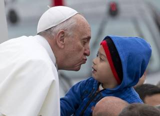 Pope Francis reaches out to kiss a child as he arrives to the Aparecida Basilicia in Aparecida, Brazil, Wednesday, July 24, 2013.