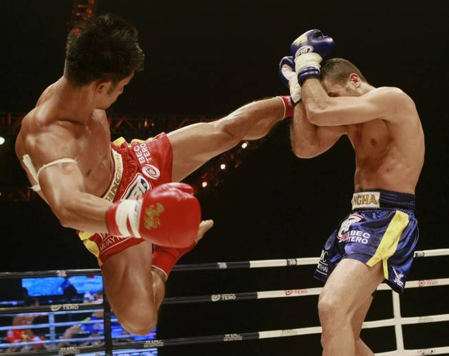 Thai champion Bigben Chor Praramhok, left, sends a high kick to French challenger Fabio Pinca during their WBC Muay Thai kick boxing welterweight title fight in Bangkok, Thailand, Saturday, June 9, 2012. Pinca won the bout on points.
