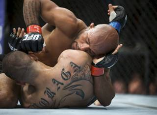 UFC flyweight champion Demetrious Johnson, top, fights John Moraga, bottom, during their bout in Seattle on Saturday, July 27, 2013. Johnson used an armbar on Moraga late in the fifth round and successfully defended his title. (AP Photo/The Seattle Times, Marcus Yam) SEATTLE OUT, USA TODAY OUT  MAGS OUT  NO SALES  TV OUT  MANDATORY CREDIT