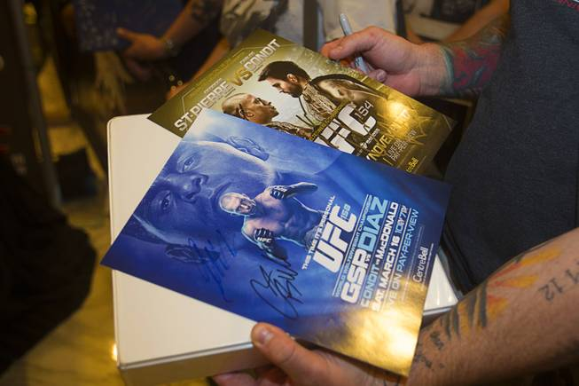 A UFC fan holds cards promoting former fights with UFC welterweight champion Georges St. Pierre of Canada during a UFC news conference in the lobby of the MGM Grand Monday, July 29, 2013. St. Pierre will defend his welterweight title against Johny Hendricks of Dallas, Texas during UFC 167 on Nov. 17 at the MGM Grand.