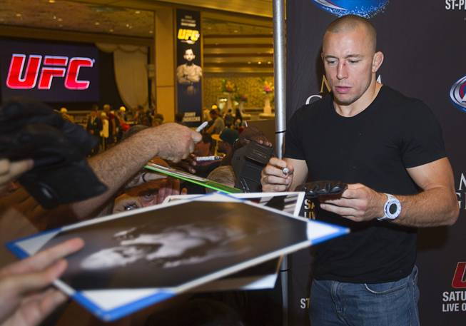 UFC welterweight champion Georges St. Pierre of Canada signs autographs for fans during a UFC news conference in the lobby of the MGM Grand on Monday, July 29, 2013. St. Pierre will defend his welterweight title against Johny Hendricks of Dallas, Texas, during UFC 167 on Nov. 17 at the MGM Grand.