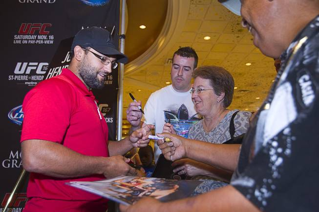 UFC fighter Johny Hendricks of Dallas, Texas signs autographs for fans during a UFC news conference in the lobby of the MGM Grand Monday, July 29, 2013. Hendricks will challenge UFC welterweight champion Georges St. Pierre of Canada for the title during UFC 167 on Nov. 17 at the MGM Grand.