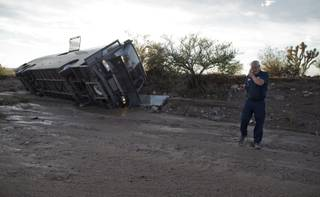 A tow truck driver talks on his cell phone after assessing the location of a tour bus which was caught in flash flood waters and pushed down a wash about 300 yards from the road, Sunday, July 28, 2013, near Dolan Springs, Ariz.