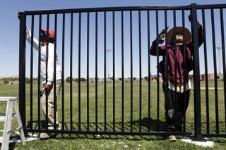 Max Alvarrez, left, and Luciano Alvarrez from Tiberti Co. Fence Division build a fence around the soccer field at Tropical Breeze Park in North Las Vegas on Tuesday, July 30, 2013.