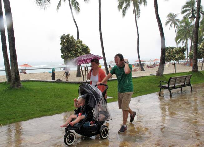 Pedestrians walk along Waikiki beach in Honolulu on Monday, July 29, 2013, as Tropical Storm Flossie approached Hawaii.