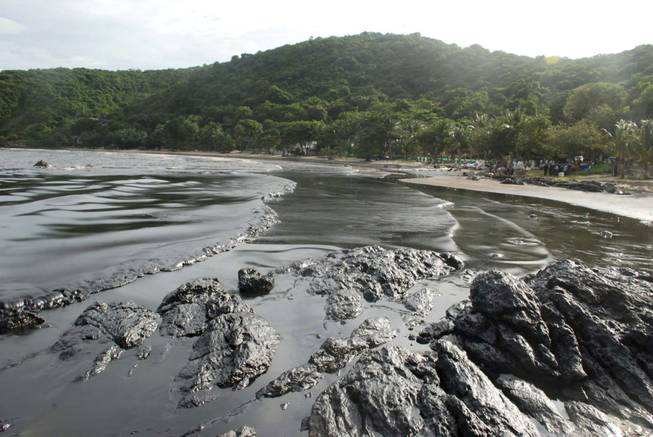 Streaks of crude oil cover the shore of Prao Bay on Samet Island in Rayong province eastern Thailand Monday, July 29, 2013. The oil spill that leaked from a pipeline has reached the popular tourist island in Thailand's eastern sea despite continuous attempts to clean it up over the weekend, officials said Monday.