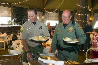 Nevada Division of Forestry firefighter Steve Clement and Metro Police resident officer Mark Baumann go through a buffet line during a free appreciation dinner for firefighters, law enforcement officers, Red Cross volunteers and Mount Charleston residents at the Resort on Mount Charleston Wednesday, July 31, 2013. The Resort on Mount Charleston hosted the dinner to thank everyone involved with fighting the Carpenter 1 wildfire.