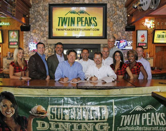 Twin Peaks announced today that an investment group led by top former Hooters executives has signed a series of development agreements to open 35 Twin Peaks restaurants throughout six states. Seated from left, Randy DeWitt, Twin Peaks Co-Founder and CEO, Seated right, Coby Brooks, La Cima Restaurants and former Hooters CEO; Standing from left, Jack Gibbons, Scott Gordon, Joe Hummel, Roger Gondek, Jim Tessmer, and Clay Mingus.