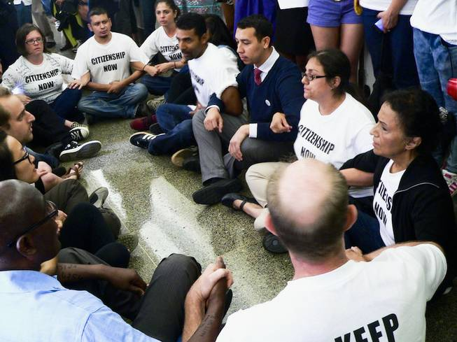 Theresa Navarro, right, and Bob Fulkerson, to her left, participate in a pro-immigration reform sit-in outside House Speaker John Boehner's office in the Longworth House Office Building in Washington, D.C., on Thursday, July 31, 2013.