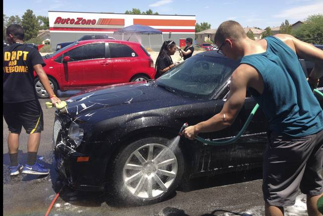 Metro Explorers hold a car wash fundraiser Saturday, Aug. 3, 2013, at Brake Masters on South Eastern Avenue to help with funeral expenses for Angel Velasquez's family.