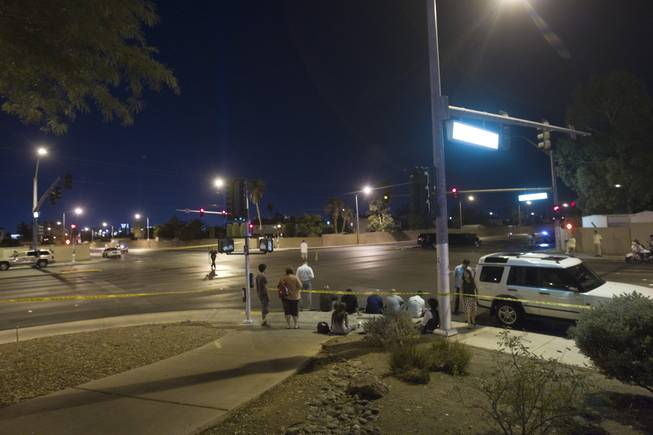People involved in the accident wait as Metro Police investigate at Rainbow Boulevard and Twain Avenue on Saturday, Aug. 3, 2013. Several people were reported injured in the accident that involved five vehicles, including a limousine.