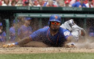 New York Mets' Jordany Valdespin slides head first into home plate to score on an RBI double by Daniel Murphy during the third inning of a baseball game against the St. Louis Cardinals Thursday, May 16, 2013, in St. Louis.