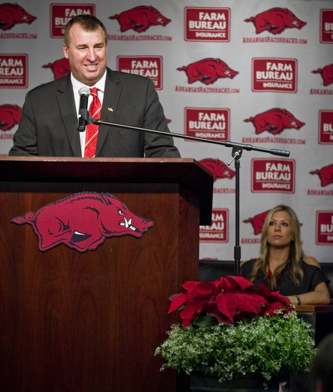 Arkansas football coach Bret Bielema, left, speaks to the media as his wife, Jen, rear right, looks on during a news conference to announce Bielema's hire in Fayetteville, Ark., Wednesday, Dec 5, 2012. Bielema, who left Wisconsin for Arkansas, will be paid $3.2 million annually for six years.