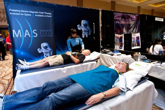 Jeff Thomson, left, and Belinda Barry try out the pulsating electro magnetic matts in the MAS booth while attending the Official Star Trek Convention at the Rio in Las Vegas on Saturday, Aug. 10, 2013.