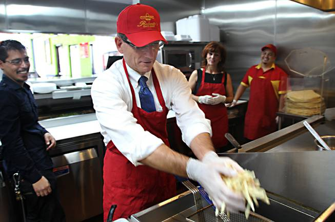 Rep. Joe Heck drops french fries into the deep fryer at Roberto's Taco Shop on Boulder Highway in Henderson on Monday, Aug. 12, 2013. Heck met with Reynaldo and Rogelio Robledo, two members of the chain's founding family, who discussed business and policy with the congressman.
