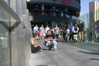 Marcus Mitchell, a local Las Vegas gambler who donates a majority of his winnings to those in need, converses with a young homeless man on a pedestrian bridge crossing the Strip, Tuesday Aug. 13, 2013.  Since the passing of his wife in 2008, Marcus has been finding ways to randomly help people he comes in contact with, either in person or online.