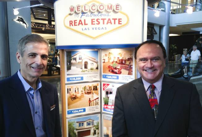 From left, 24/7 Real Estate brokers George Kleanthis and Tony Keep pose for a photo at their company's kiosk at Las Vegas' Fashion Show mall on Aug. 5, 2013.