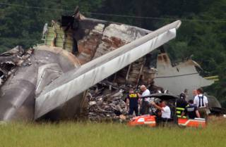 NTSB investigators work around the tail section of the UPS cargo plane that crashed on approach to the Birmingham-Shuttlesworth International Airport August 15,  2013 in Birmingham, Ala.