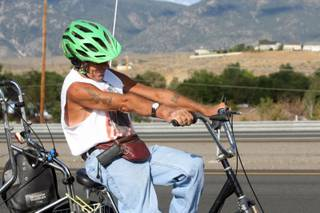 In this Aug. 8, 2013 photo, Glenn Lucky rides north on Highway 395 near Sunridge, Nev. At 60, Lucky has slowed just a little, friends say, but his tanned arms remain chiseled by his near-daily bicycle rides between Indian Hills and downtown Carson City.