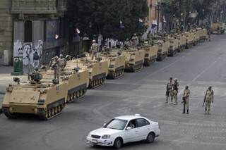 Egyptian army soldiers take their positions on top and next to their armored vehicles while guarding an entrance to Tahrir Square, in Cairo, Friday, Aug. 16, 2013.