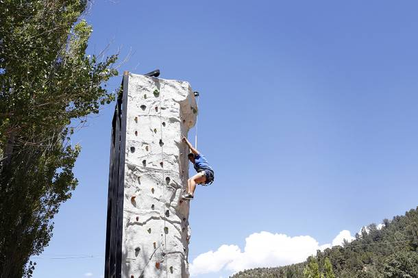 Camper Stephanie Diaz, 15, climbs the rock wall at Camp Heart and Sole at Torino Ranch in Lovell Canyon on Saturday, August 17, 2013.
